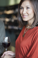 Mixed race woman drinking wine at bar