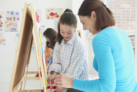 Teacher helping student paint in art class