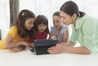 Teacher and students using digital tablet together