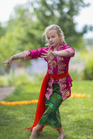 Caucasian girl performing Balinese dance in backyard