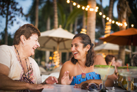 Mother and daughter laughing at outdoor table 11018050101| 写真素材・ストックフォト・画像・イラスト素材|アマナイメージズ
