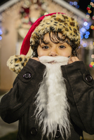 Hispanic girl wearing white beard and Santa hat outside house decorated with string lights