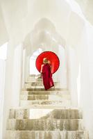 Asian Buddhist monk carrying umbrella on staircase at Hsinbyume Pagoda, Mandalay, Sagaing, Myanmar