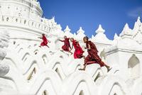 Asian monks running on white temple walls, Hsinbyume Pagoda, Mandalay, Sagaing, Myanmar