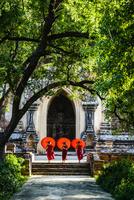 Asian Buddhist monks carrying umbrellas on staircase at Hsinbyume Pagoda, Mandalay, Sagaing, Myanmar