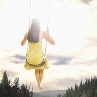 Mixed race woman admiring view from swing