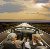 Older Hispanic couple driving on rural road in desert landscape