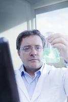 Hispanic scientist examining beaker in lab 11018051238| 写真素材・ストックフォト・画像・イラスト素材|アマナイメージズ