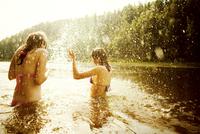 Girls splashing together in lake