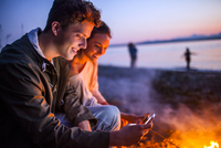 Caucasian couple using cell phone together near fire on beach