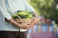 Older Filipino woman carrying basket of cucumbers