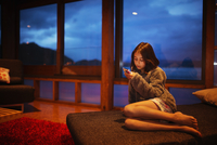 Mixed race girl using cell phone in living room 11018051529| 写真素材・ストックフォト・画像・イラスト素材|アマナイメージズ