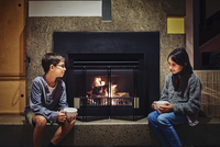 Mixed race children having hot drink together near fireplace