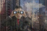 Hispanic businessman looking through binoculars at office window 11018051607| 写真素材・ストックフォト・画像・イラスト素材|アマナイメージズ