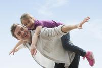 Caucasian father carrying daughter piggyback outdoors 11018051669| 写真素材・ストックフォト・画像・イラスト素材|アマナイメージズ