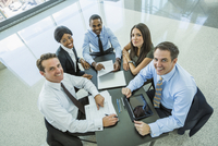 High angle view of business people smiling in meeting 11018051751| 写真素材・ストックフォト・画像・イラスト素材|アマナイメージズ