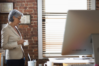 Hispanic businesswoman drinking cup of coffee in office
