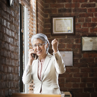 Hispanic businesswoman cheering in office 11018052438| 写真素材・ストックフォト・画像・イラスト素材|アマナイメージズ