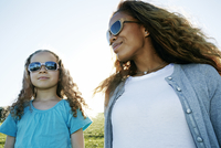 Mother and daughter wearing sunglasses outdoors