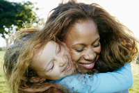 Mother and daughter hugging outdoors