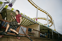 Caucasian man skateboarding with paddle pole at amusement park