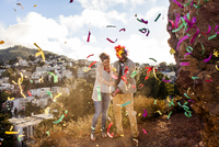 Couple throwing confetti on hill overlooking cityscape 11018052688| 写真素材・ストックフォト・画像・イラスト素材|アマナイメージズ