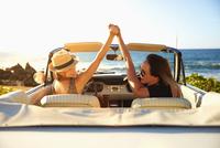 Women cheering in convertible on beach 11018052808| 写真素材・ストックフォト・画像・イラスト素材|アマナイメージズ