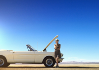 Caucasian woman stranded with broken down convertible on remote road