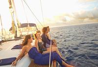 Friends dangling legs over yacht deck 11018052920| 写真素材・ストックフォト・画像・イラスト素材|アマナイメージズ