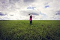 Caucasian girl playing in grassy field