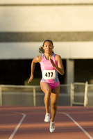 Female runner competing on racetrack