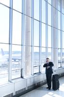 Caucasian businessman talking on cell phone in airport 11018053928| 写真素材・ストックフォト・画像・イラスト素材|アマナイメージズ