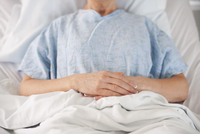 Midsection of Caucasian patient laying in hospital bed