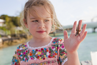 Caucasian girl holding lizard on her hand