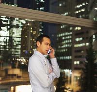 Hispanic businessman talking on cell phone in office at night 11018054073| 写真素材・ストックフォト・画像・イラスト素材|アマナイメージズ