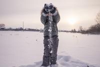 Mari boy in parka playing in snowy field 11018055100| 写真素材・ストックフォト・画像・イラスト素材|アマナイメージズ