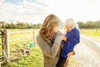Caucasian mother tickling daughter on rural road 11018055249| 写真素材・ストックフォト・画像・イラスト素材|アマナイメージズ