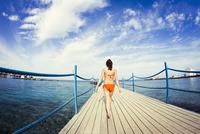 Caucasian girl walking on wooden dock over sea 11018055375| 写真素材・ストックフォト・画像・イラスト素材|アマナイメージズ