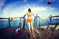 Caucasian girl standing at ladder over ocean 11018055377| 写真素材・ストックフォト・画像・イラスト素材|アマナイメージズ