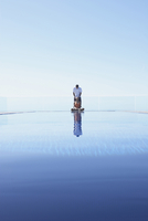 Couple relaxing near infinity pool overlooking scenic view 11018055422| 写真素材・ストックフォト・画像・イラスト素材|アマナイメージズ