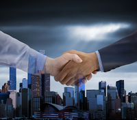 Businesspeople shaking hands over city skyline