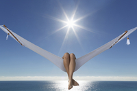 Caucasian woman laying in hammock near ocean under blue sky 11018055782| 写真素材・ストックフォト・画像・イラスト素材|アマナイメージズ