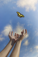 Caucasian woman reaching for butterfly in blue sky