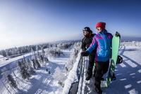 Caucasian snowboarders standing on snowy mountaintop 11018055824| 写真素材・ストックフォト・画像・イラスト素材|アマナイメージズ