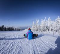 Caucasian snowboarder sitting on snowy slope 11018055826| 写真素材・ストックフォト・画像・イラスト素材|アマナイメージズ