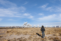 Hispanic woman walking to satellites in remote field