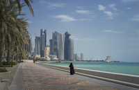 Woman walking on Doha waterfront, Doha, Qatar