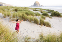 Caucasian girl running with arms outstretched on beach