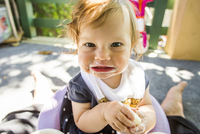 Caucasian baby girl eating on patio