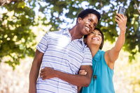 Couple taking selfie with cell phone outdoors